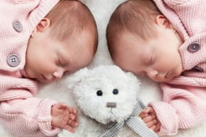 Newborn twins sisters sleeping on white fur with a teddy bear in the middle.