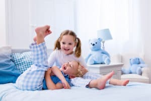 Happy kids playing in white bedroom. Little boy and girl, brother and sister play on the bed wearing pajamas. Nursery interior for children. Nightwear and bedding for baby and toddler. Family at home.